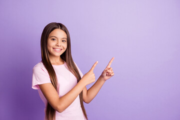Photo of optimistic nice brunette girl point empty space wear t-shirt isolated on pastel purple color background Wall mural