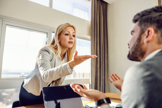 Businesswoman standing at the office and having a disagreement with her colleague who is sitting in elegant clothes in front of a laptop. Issues at work, disagreement