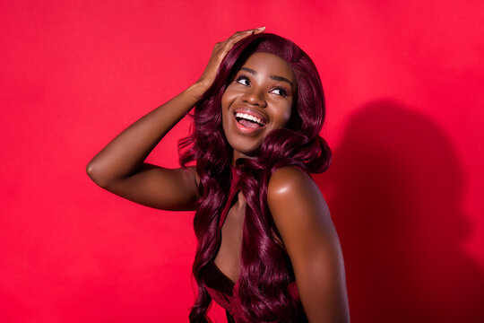Photo of attractive nice afro american young woman look empty space hold hand empty space isolated on red color background