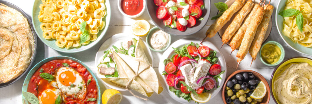 Set of different Mediterranean foods: olives, mozzarella and tomato salad, Greek salad, pasta, tortellini ravioli, pizza, pita lavash sandwich, shish kebab, shakshuka, hummus, top view