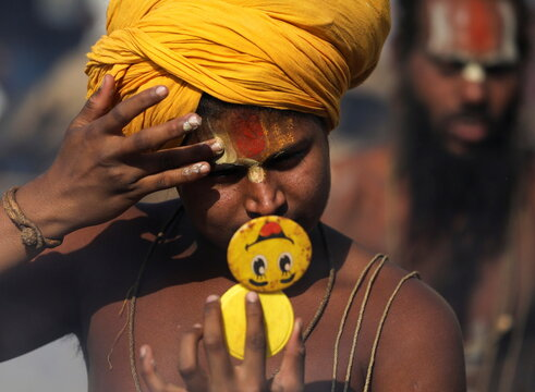Sadhu, or a Hindu holy man, looks into a mirror as he prepares for morning prayers during Kumbh Mela, amid the spread of COVID-19, in Haridwar