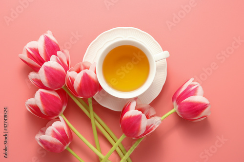 white cup of tea with pink tulips top view at the pink background, copy space for the text, beautiful spring background, mother day or romantic theme