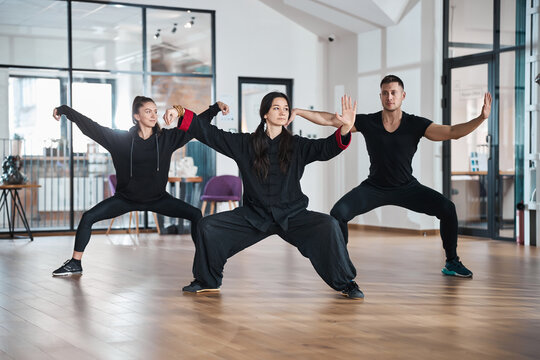 Tai chi students with teacher training single whip form