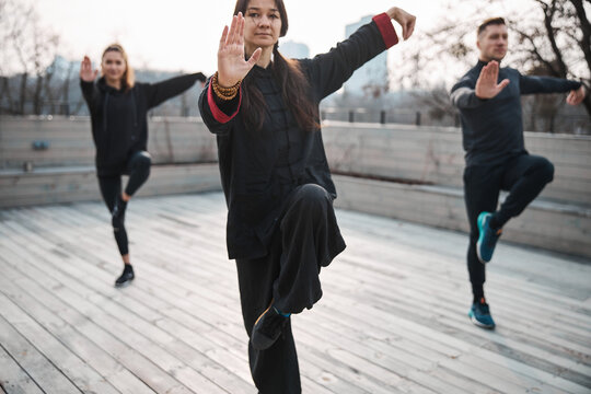Woman master of tai chi holding balance with two people