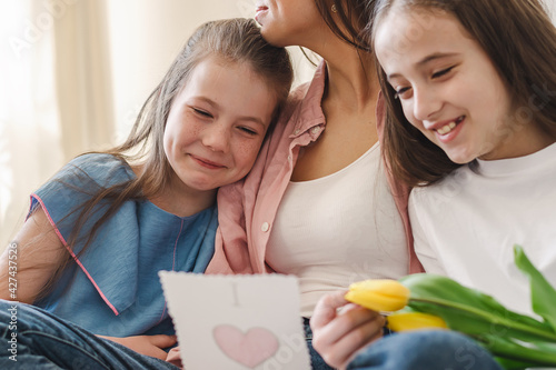 Happy dark-haired young woman embraces her daughters sitting at home on the couch.In their hands is a bouquet of yellow flowers and a homemade gift.The concept of Mother's Day, March 8 and Birthday.