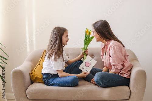 A dark-haired girl congratulates her mother on Mother's Day, gives her bouquet of yellow tulips and homemade greeting card.Home interior design.The concept of Mom's Day,March 8 and Birthday.Copy space