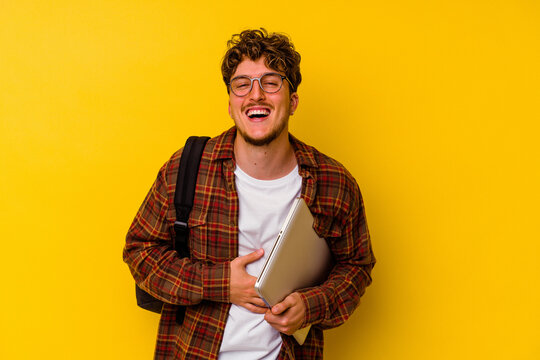 Young student caucasian man holding a laptop isolated on yellow background laughing and having fun.