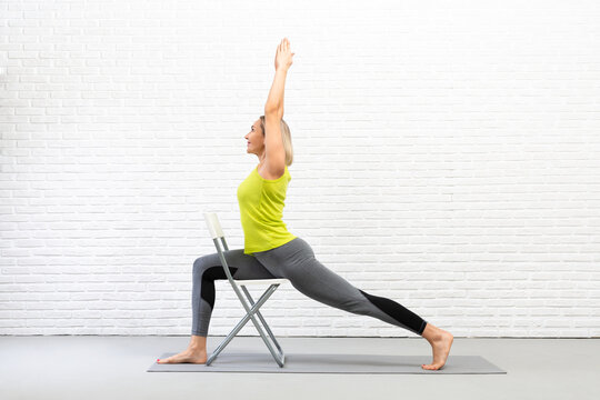 Yoga with a chair. Fit caucasian woman practice warrior pose using props in loft white studio indoor.