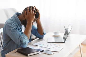 Fototapeta Stressed Black Entrepreneur Sitting At Desk And Looking At Financial Papers