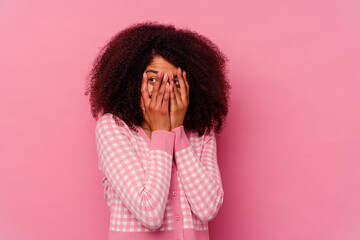 Fototapeta Young african american woman isolated on pink background blink through fingers frightened and nervous.