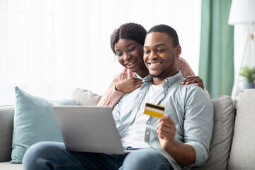 Fototapeta Cheerful young black man and woman shopping online, copy space