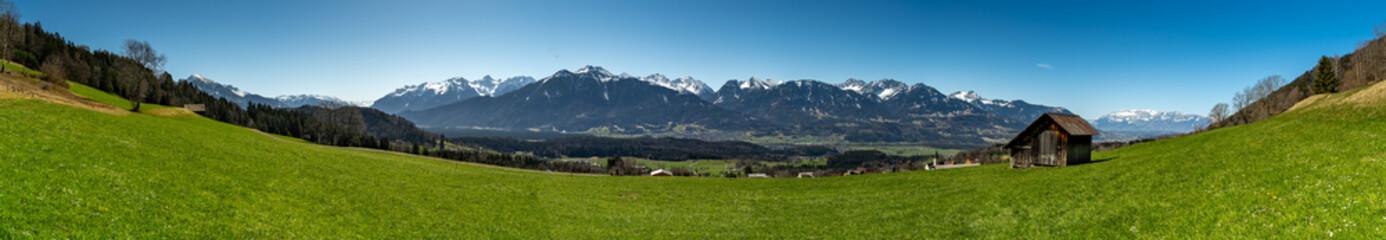 Fototapeta Panorama Aussicht über das Tal auf die verschneiten Berge von Brand und Nenzing. Wiesen mit Frühlingsblumen und Bäumen an einem sonnigen Tag. Walgau im besten Licht. Vorarlberg