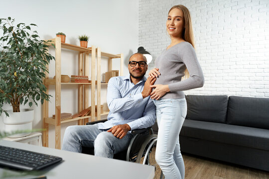Pregnant woman holding a hand of her disabled husband sitting in a wheelchair
