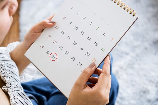 woman hand holding calendar planning for due date payment, tax ,pay day concept