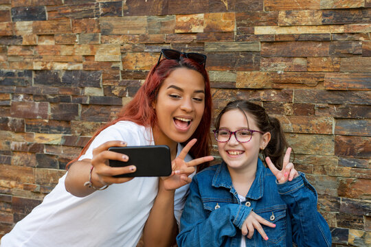 young latina woman and caucasian girl taking selfie