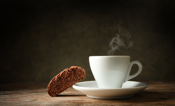 Lonely coffee break. Chocolate biscuit and steaming espresso cup in dark setting, space for text.