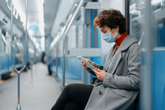 young woman with a digital tablet sitting in an empty subway car.