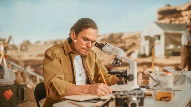 Archaeological Digging Site: Male Archeologist Doing Indigenous Culture Research, Discovers Ancient Civilization Historical Artifacts, Fossil Remains at Excavation Site, Study it Under Microscope