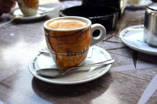 Café negro en una taza pequeña sobre un plato y cuchara