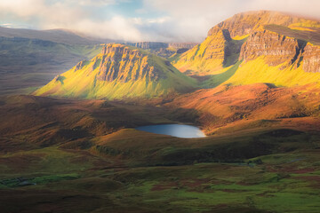 Fototapeta Vibrant golden light over epic mountain landscape of the rugged, contoured terrain of the Cleat and Dun Dubh at the Quiraing on the Isle of Skye, Scotland.