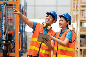 Group of Asian young male and female employee warehouse worker in safety vest and helmet working with tablet for checking products or parcel goods on shelf pallet in industry factory warehouse