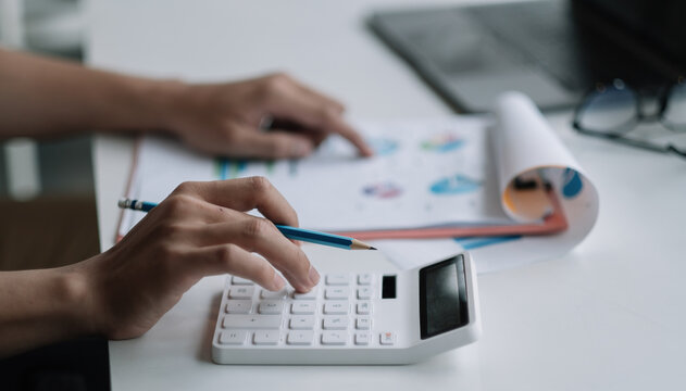 Close up businessman using calculator for analysis maketing plan, Accountant calculate financial report, computer with graph chart. Business, Finance and Accounting concept.