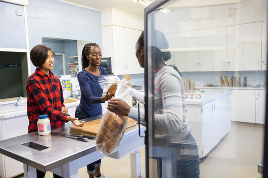Teenage volunteers making sandwiches in community center kitchen
