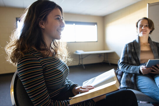 Smiling teen girl reading in book club meeting in community center