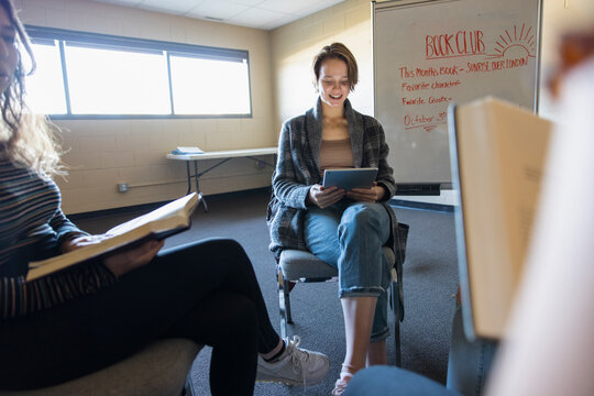 Teen girl with digital tablet reading in book club meeting circle