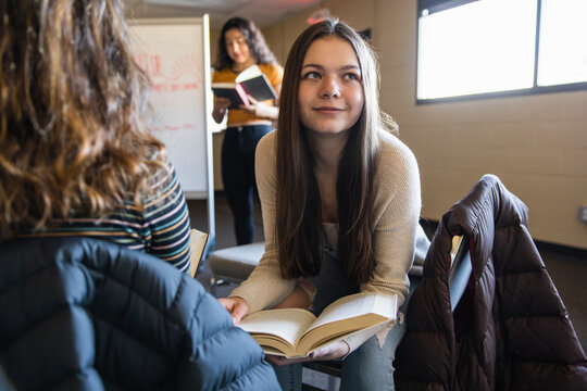 Smiling girl reading in book club meeting