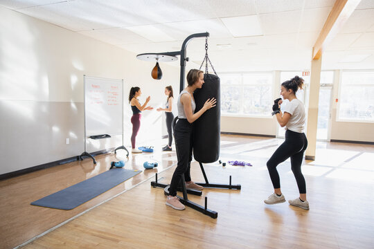 Teen girls kickboxing at punching bag in gym studio