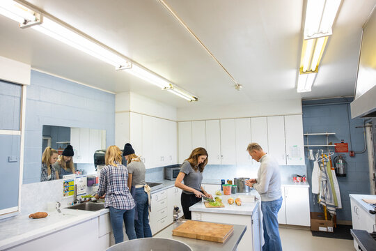 Family volunteers cooking in community center soup kitchen