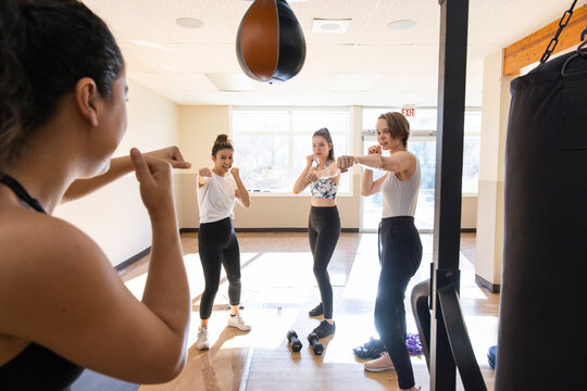 Teen girls practicing boxing fighting stance in gym studio