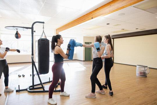 Teen girls practicing boxing in gym studio