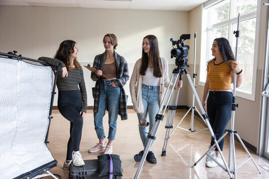 High school girl students preparing video equipment in classroom