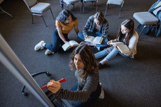 Teen girls reading and writing on whiteboard in book club meeting