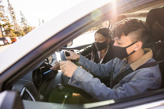 Driving instructor and student in face masks in car