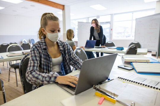High school girl student in face mask using laptop in classroom