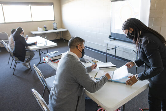 Teacher helping mature student in mask in community center classroom