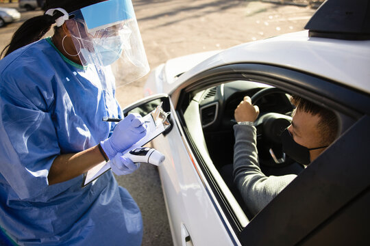 Nurse in PPE with clipboard and thermometer talking to patient in car