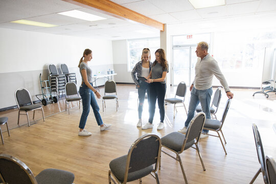Family volunteers arranging chairs in circle in community center