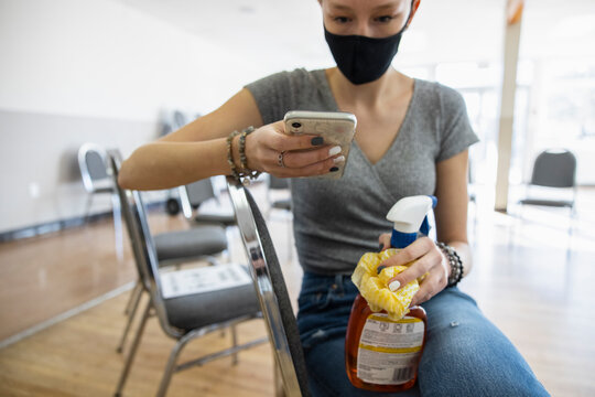 Teen girl in face mask with smart phone cleaning community center
