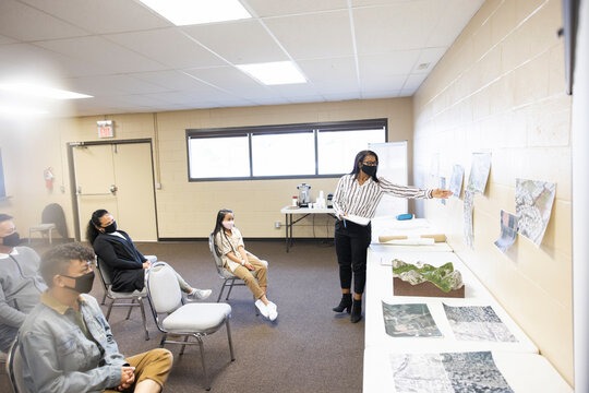 Woman in face mask leading urban planning meeting in community center