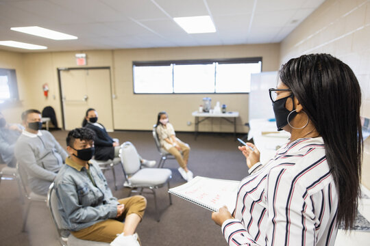 Woman in face mask leading meeting in community center