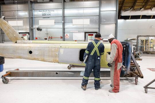 Engineers working on helicopter in hangar