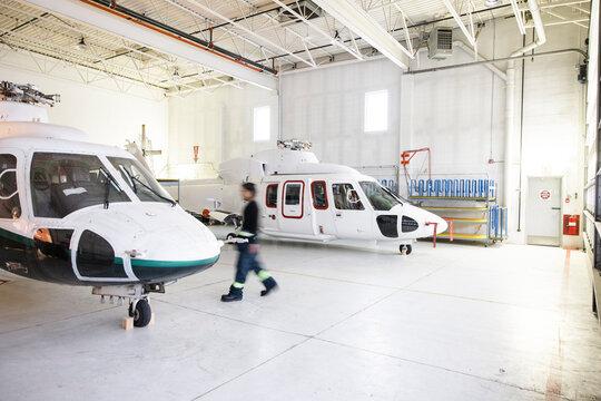 Man walking between helicopters in hangar