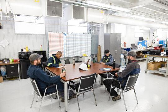 Engineers sitting around meeting table in workshop