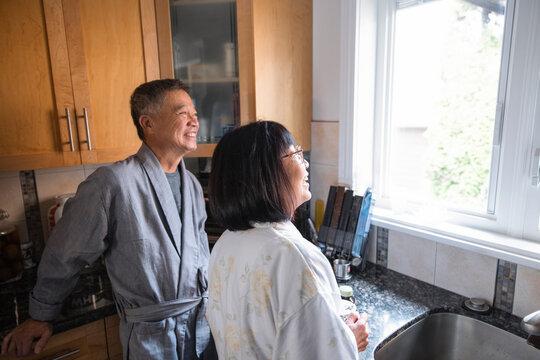 Senior couple in bathrobe looking out kitchen window