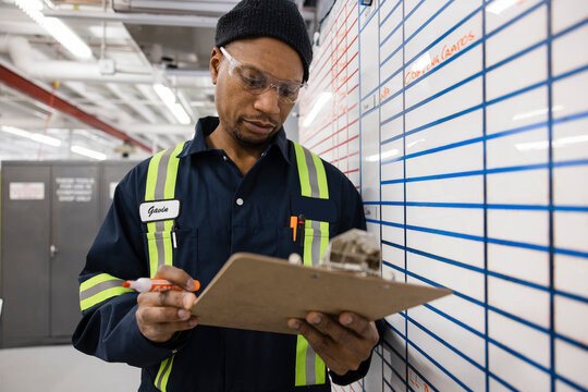 Technician checking wall planner against checklist