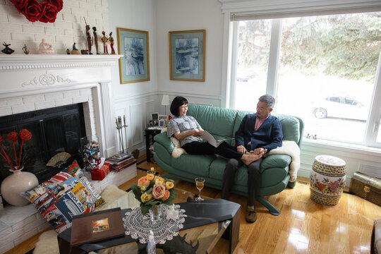 Senior couple relaxing with magazine on sofa